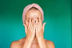 La jeune femme blanche met dessus un masque protecteur à la maison sur un fond de turquoise Femme européenne se lavant le visage  image libre de droits