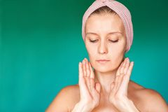La jeune femme blanche met dessus un masque protecteur à la maison sur un fond de turquoise Femme européenne se lavant le visage  photo stock