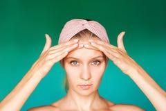 La jeune femme blanche met dessus un masque protecteur à la maison sur un fond de turquoise Femme européenne se lavant le visage  image stock