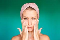 La jeune femme blanche met dessus un masque protecteur à la maison sur un fond de turquoise Femme européenne se lavant le visage  photographie stock