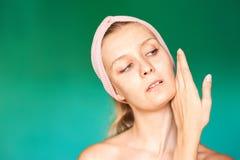 La jeune femme blanche met dessus un masque protecteur à la maison sur un fond de turquoise Femme européenne se lavant le visage  images stock