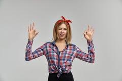 La jeune femme blonde attirante mince cligne de l'oeil et montre le signe CORRECT portrait de studio sur le fond d'isolement photographie stock libre de droits