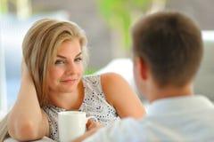 La jeune femme blonde aux cheveux longs belle s'asseyant sur un divan a étayé sa tête avec une main et tenir une tasse de thé dél Photos stock