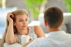 La jeune femme blonde aux cheveux longs belle s'asseyant sur un divan a étayé sa tête avec une main et tenir une tasse de thé dél Images stock
