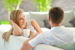 La jeune femme blonde aux cheveux longs belle s'asseyant sur un divan a étayé sa tête avec une main et tenir une tasse de thé dél Photo stock