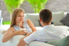 La jeune femme blonde aux cheveux longs belle s'asseyant sur un divan a étayé sa tête avec une main et tenir une tasse de thé dél Photographie stock libre de droits