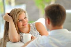 La jeune femme blonde aux cheveux longs belle s'asseyant sur un divan a étayé sa tête avec une main et tenir une tasse de thé dél Images libres de droits