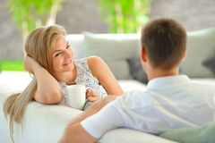 La jeune femme blonde aux cheveux longs belle s'asseyant sur un divan a étayé sa tête avec une main et tenir une tasse de thé dél Image stock