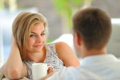 La jeune femme blonde aux cheveux longs belle s'asseyant sur un divan a étayé sa tête avec une main et tenir une tasse de thé dél Image libre de droits