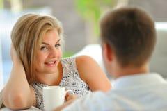 La jeune femme blonde aux cheveux longs belle s'asseyant sur un divan a étayé sa tête avec une main et tenir une tasse de thé dél Photo libre de droits