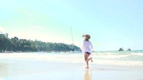 La jeune femme blonde avec le chapeau et la tunique blanche se déplace sur la plage thaïlandaise clips vidéos