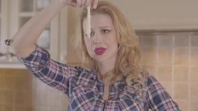 La jeune femme blonde avec le rouge à lèvres rouge, les longs cheveux ayant le morceau de pâte actuel et le regardent aiment à qu clips vidéos