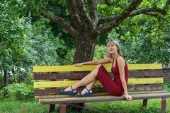 La jeune femme blonde dans un penchement rouge de robe s'assied sur un banc en bois images stock
