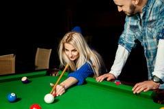 La jeune femme blonde de beauté joue billiar pour la première fois avec Photo stock
