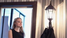 La jeune femme blonde de sourire joyeuse prend la veste outre du support de vêtements dans le couloir clips vidéos