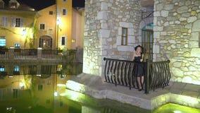La jeune femme blonde flirte, séduit, se tient sur le balcon du vieux bâtiment dans la ville antique la nuit Fille sexy dans pelu banque de vidéos