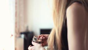 La jeune femme blonde met la pile de bracelets sur le bras dans le salon clips vidéos