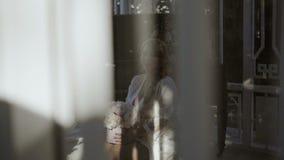 La jeune femme blonde mignonne dans la lingerie se reposant avec le bouquet de fleurs a tiré par la fenêtre banque de vidéos