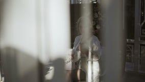 La jeune femme blonde mignonne dans la lingerie se reposant avec le bouquet de fleurs a tiré par la fenêtre clips vidéos