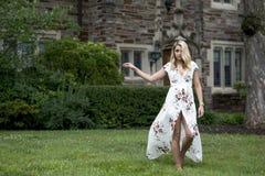 La jeune femme blonde renversante pose dans la robe blanche d'impression florale photos libres de droits