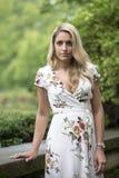 La jeune femme blonde renversante pose dans la robe blanche d'impression florale photographie stock