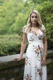 La jeune femme blonde renversante pose dans la robe blanche d'impression florale images stock