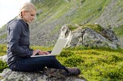 La jeune femme blonde s'assied avec un ordinateur portatif sur une pierre Photo stock