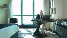 La jeune femme blonde sexy d'affaires boit du thé dans la chambre d'hôtel ou le bureau et appelle par le mobile Voyage d'affaires clips vidéos