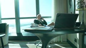 La jeune femme blonde sexy fâchée d'affaires boit du thé dans la chambre d'hôtel ou le bureau, parle et crie par le mobile banque de vidéos