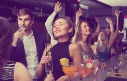 La jeune femme boit des cocktails avec le collègue Photographie stock