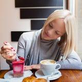 La jeune femme boit du café de matin avec le dessert de croissant et de mousse de lumière Images libres de droits