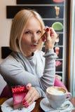 La jeune femme boit du café de matin avec le dessert de croissant et de mousse de lumière Image libre de droits