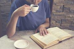 La jeune femme boit du café tout en lisant un livre Photos stock