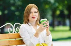 La jeune femme boit du café en parc Photographie stock