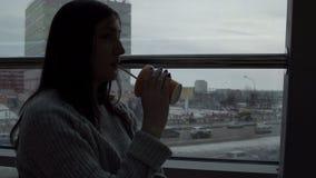 La jeune femme boit du jus fraîchement serré dans un café, regardant la fenêtre sur le fond de mégalopole banque de vidéos