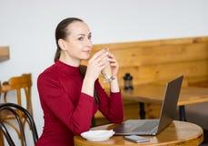 La jeune femme boit du latte en café avec l'ordinateur portable et le téléphone portable Photos stock