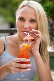 La jeune femme boit le cocktail extérieur un après-midi chaud d'été dedans Photographie stock libre de droits