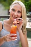 La jeune femme boit le cocktail extérieur un après-midi chaud d'été dedans Image stock