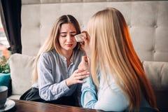 La jeune femme calme son amie en café Images stock