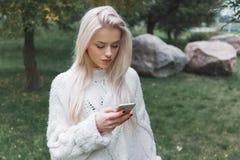 La jeune femme caucasienne de cheveux blonds dans le pull blanc utilise le téléphone extérieur photo libre de droits