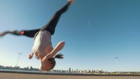 La jeune femme caucasienne exécute la secousse acrobatique sur l'asphalte sur le paysage urbain de fond clips vidéos