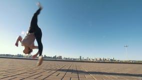La jeune femme caucasienne exécute la secousse acrobatique sur l'asphalte sur le paysage urbain de fond banque de vidéos