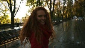 La jeune femme caucasienne marchant en parc coloré d'automne par l'allée humide, appréciant le feuillage d'automne, tourne autour banque de vidéos