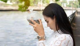 La jeune femme caucasienne prient des poissons de libération à la rivière dans le matin en vacances photographie stock