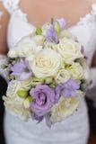 La jeune femme caucasienne s'est habillée dans le blanc, tenant une grande composition florale nuptiale pour le grand jour Photos libres de droits
