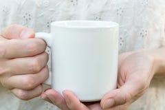 La jeune femme caucasienne tenant une tasse blanche, raillent, espace vide pour le texte, illustration, mains, chemise de toile Photo stock