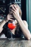 La jeune femme caucasienne tient le téléphone intelligent devant le visage se reposant sur la table en café, bocal avec le cockta image libre de droits