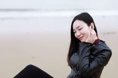 La jeune femme chinoise asiatique écoutent la musique se reposent sur la plage de sable photo stock