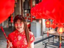 La jeune femme chinoise avec l'habillement de tradition tenant des bâtons d'encens exaspèrent, nouvelle année chinoise photos libres de droits
