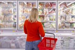 La jeune femme choisit des marchandises dans un étalage de supermarché photos libres de droits